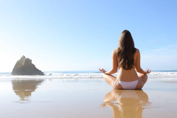 Rückblick auf eine Frau im Bikini, die Yoga-Übung macht – Foto
