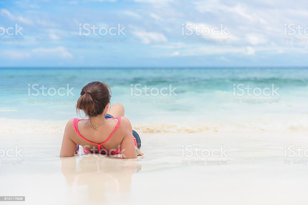 back view of a woman lying on beach stock photo