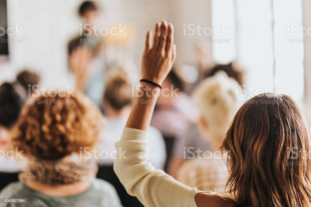 Back view of a woman raising her arm on a seminar. stock photo