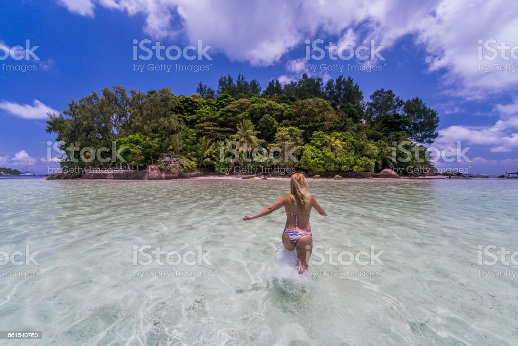Back view of a woman running through the sea. royalty-free stock photo