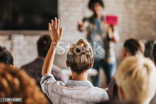 istock Back view of a woman wants to ask a question on a seminar. 1138142697