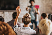 Rear view of casual businesswoman raising her hand to ask the question on education event in a board room.