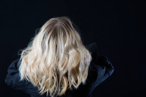 Back View Of A Woman With Platinum Blonde Hair with Dark Roots Back View Of A Woman With Platinum Blonde Hair with Dark Roots highlights hair stock pictures, royalty-free photos & images