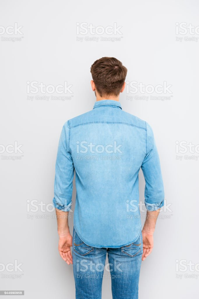 Back view of a young casual man isolated on gray background stock photo