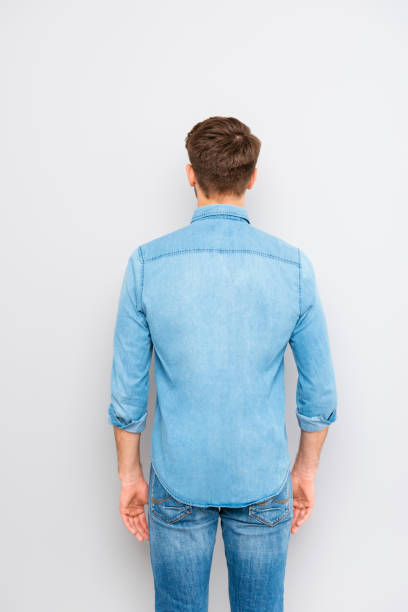 Back view of a young casual man isolated on gray background Back view of a young casual man isolated on gray background bending over backwards stock pictures, royalty-free photos & images