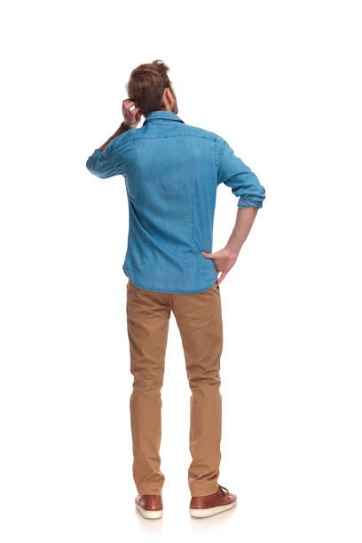 widok z tyłu młodego przypadkowego mężczyzny drapającego głowę - plecy zdjęcia i obrazy z banku zdjęć
