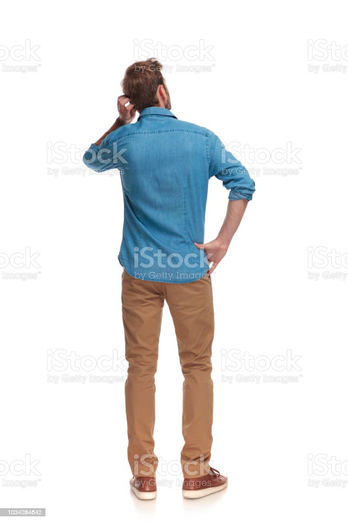 back view of a young casual man scratching his head stock photo