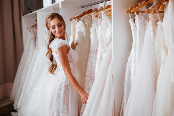 Back view of a young woman in wedding dress looking at bridal gowns stock photo