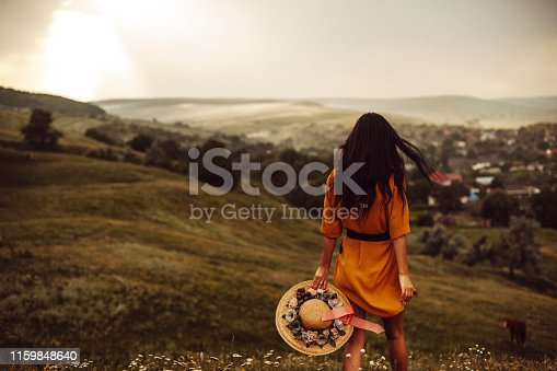Back view of a young woman with dark long hair holding a hat and walking down the hill against sunset.