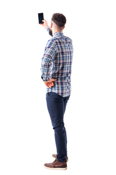 back view of adult man taking photo or selfie with smartphone - rear view stock photos and pictures