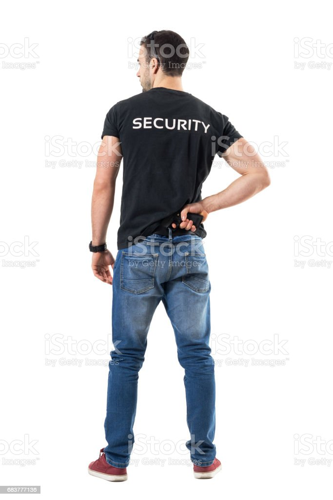 Back view of alerted undercover cop or security agent reaching hand gun attached on belt stock photo