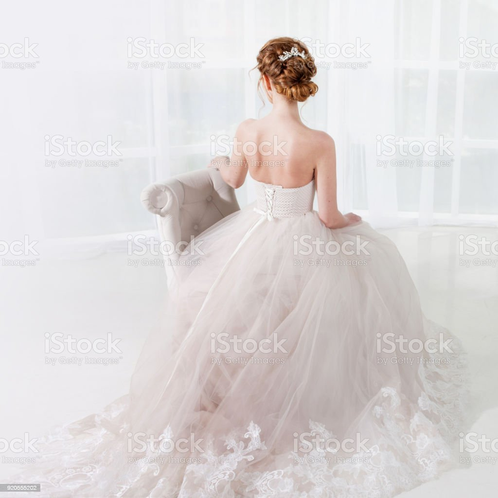 Vista trasera del increíble novia joven. Asiento rojo mujer cabeza en la silla. Peinado elegante. - foto de stock