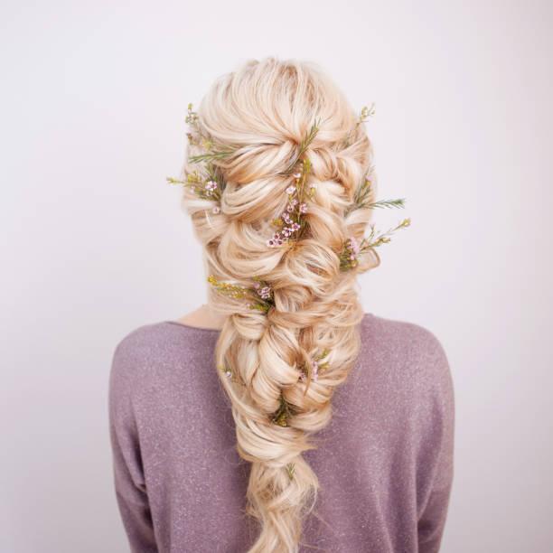 Vista posterior de un elegante peinado de moda, rizos de entrelazado y decoración con pétalos de flores - foto de stock
