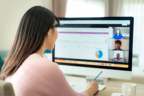 Back view of Asian business woman talking to her colleagues about plan in video conference. Multiethnic business team using computer for a online meeting in video call. Group of people smart working from home. Back view of Asian business woman talking to her colleagues about plan in video conference. Multiethnic business team using computer for a online meeting in video call. Group of people smart working from home. desolation stock pictures, royalty-free photos & images