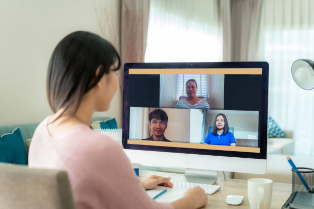 back view of asian business woman talking to her colleagues about plan in video conference. multiethnic business team using computer for a online meeting in video call. group of people smart working from home. - social distancing stock pictures, royalty-free photos & images