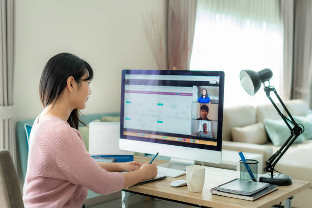 back view of asian business woman talking to her colleagues about plan in video conference. multiethnic business team using computer for a online meeting in video call. group of people smart working from home. - work from home stock pictures, royalty-free photos & images