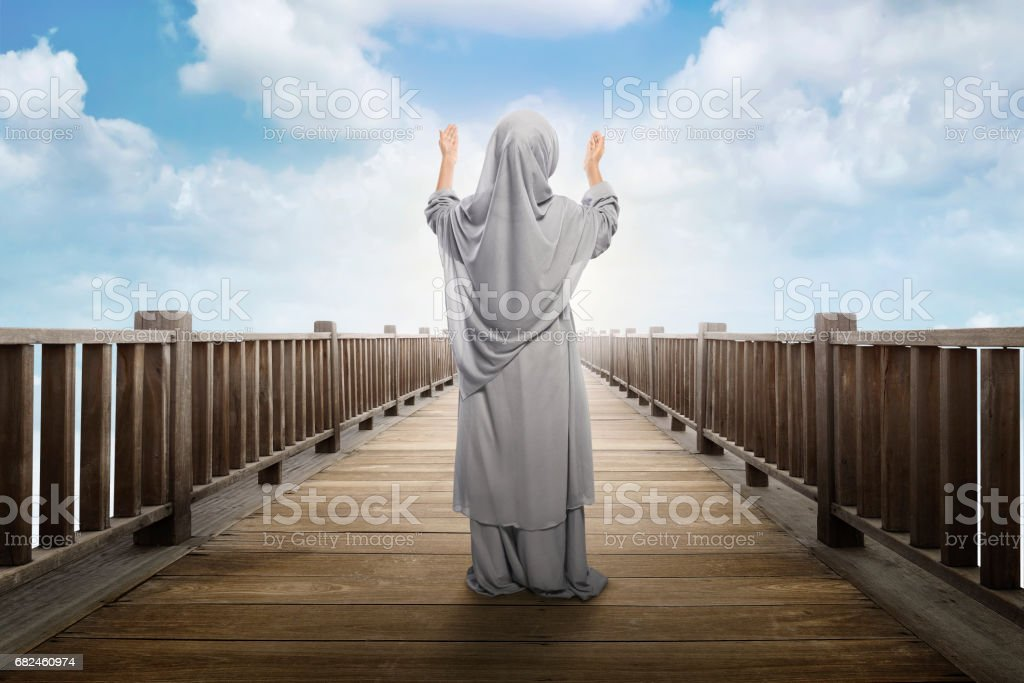 Back view of asian muslim girl standing and praying to god royalty-free stock photo