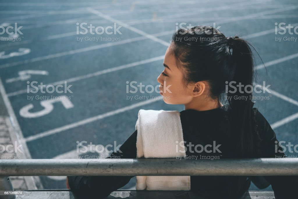 back view of asian sportswoman with towel on running track on stadium Lizenzfreies stock-foto