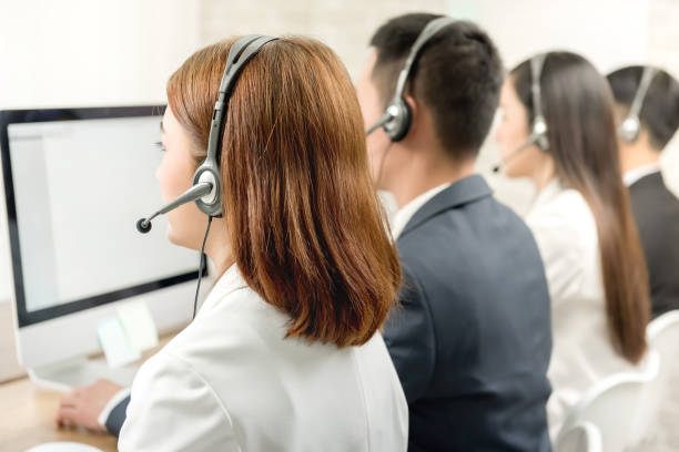 Back view of Asian telemarketing customer service agent team stock photo