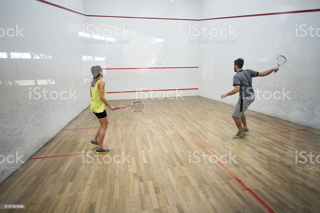 Back view of athletes playing racketball on a court. stock photo