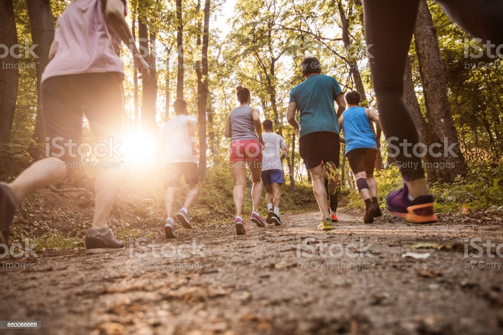 Back view of athletes running in nature while taking part in marathon race. stock photo