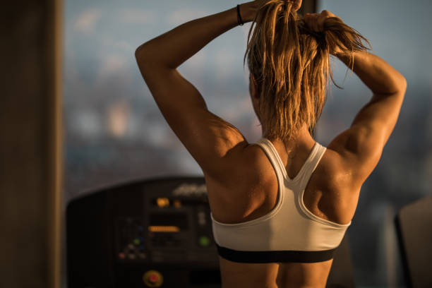 Back view of athletic woman making ponytail before sports training in a gym. Rear view of muscular build woman tightening her ponytail before exercising on treadmill in a health club. tighten stock pictures, royalty-free photos & images