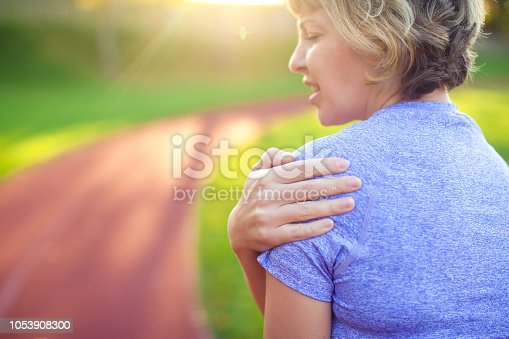 istock Back view of athletic young woman in sportswear touching her painful neck at the stadium. Sport, health and people concept 1053908300