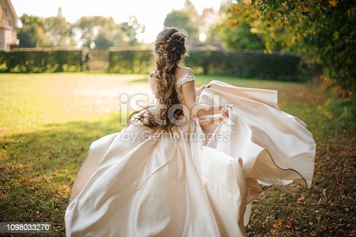 Back view of beautiful bride spinning in a wedding dress dancing on the green field on sunny day