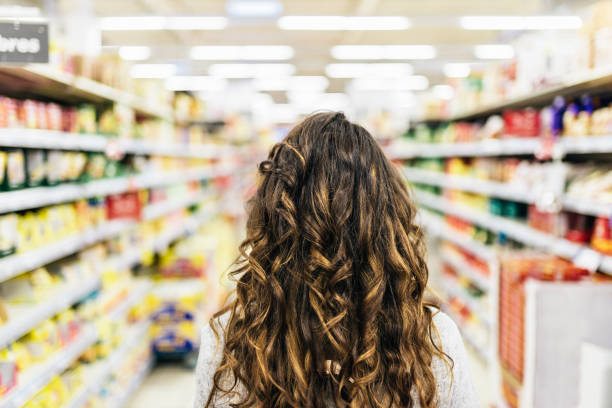 Back view of Beautiful woman buying food in supermarket. stock photo