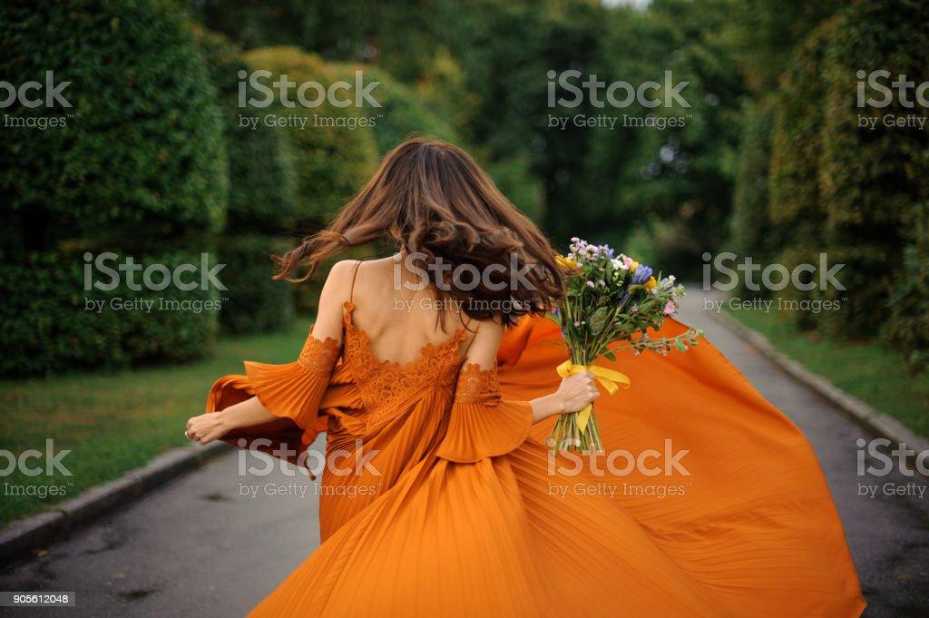 Rückansicht der schönen Frau im langen orangen Kleid – Foto