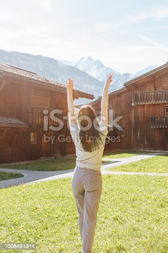 istock back view of beautiful young woman raising hands while standing between wooden houses in mountain village, mont blanc, alps 1008491314