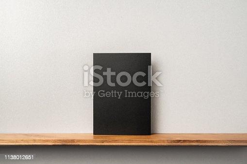 1172913655istockphoto back view of black magazine stand on bookshelf 1138012651