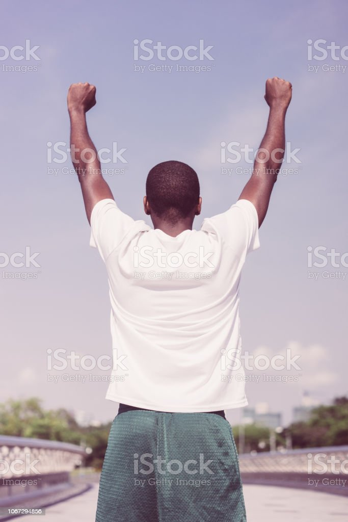 Back view of black man celebrating sport success. Young Afro American...