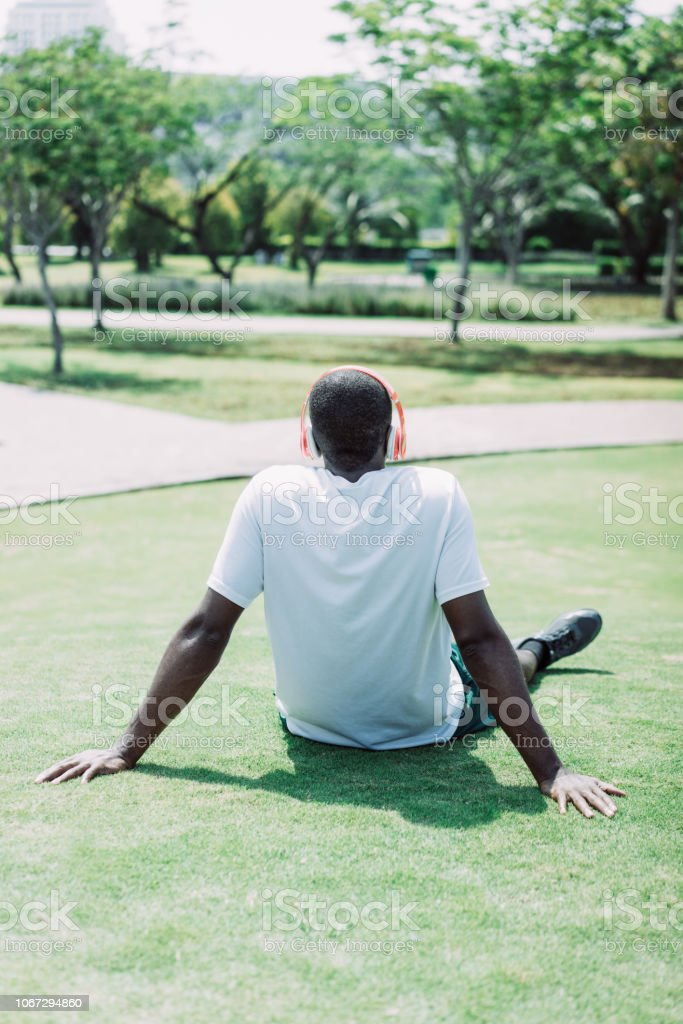 Back view of black man resting on grass with wireless headphones....