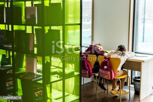 istock back view of bored schoolgirls lying on table in library 1088956078