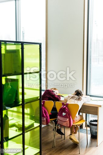 istock back view of bored schoolgirls sleeping on desk in library 1088956068