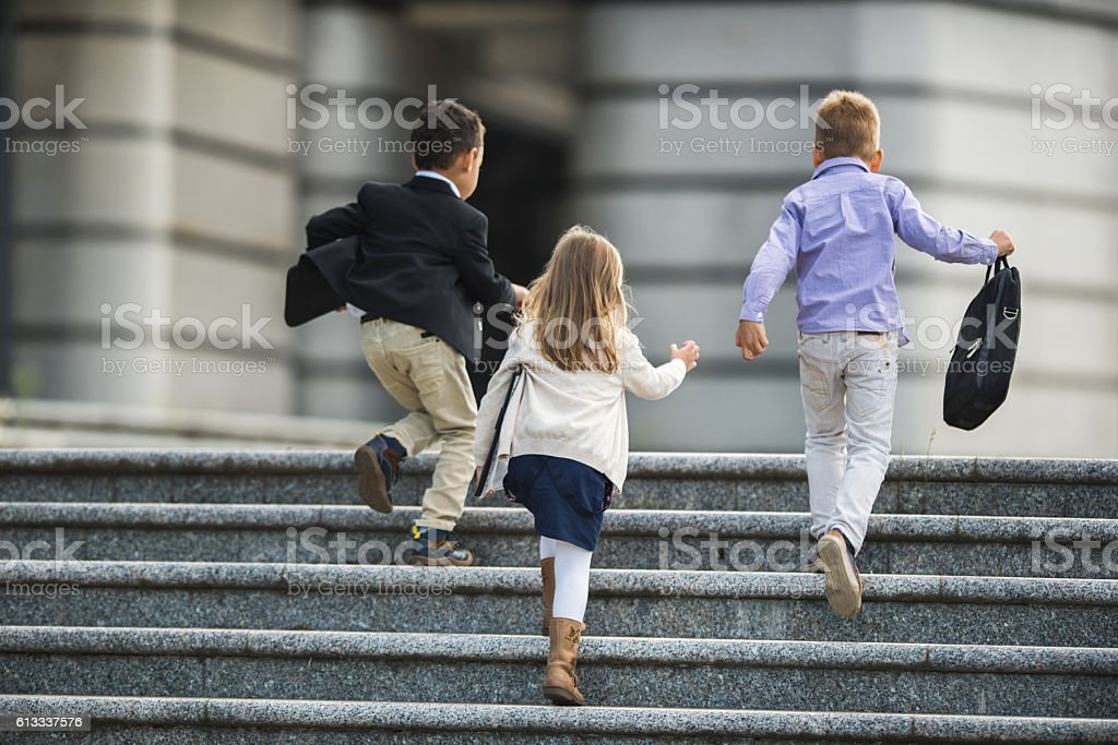 Back view of business kids running up the stairs. - foto de acervo