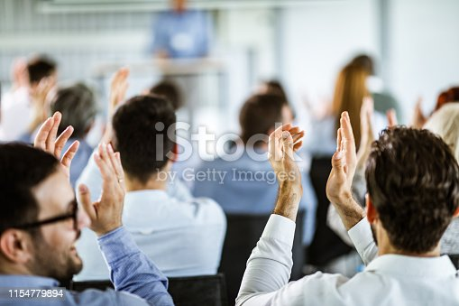 894290604 istock photo Back view of business people applauding on a seminar. 1154779894