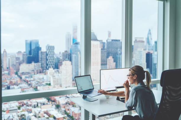 Back view of business woman sitting at panoramic skyscraper office desktop front PC computer with financial graphs and statistics on monitor. Analysis of digital market and investment in block chain stock photo