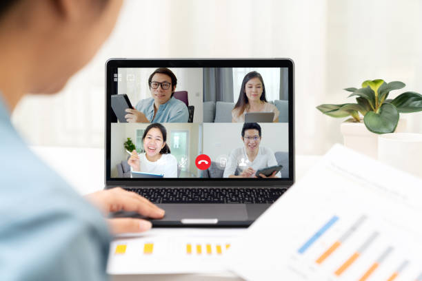 Back view of business woman talking and discussion in video conference. Asian team using laptop and tablet online meeting in video call.Working from home, Working remotely and Self-isolation. stock photo