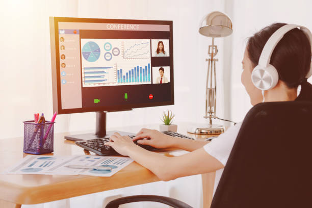 back view of business woman talking to her colleagues about plan in video conference. - remote work imagens e fotografias de stock