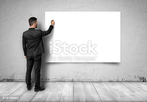 istock Back view of businessman drawing at white empty canvas on 519185652
