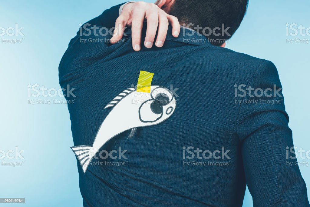 back view of businessman in suit with paper made fish on back, april fools day concept stock photo