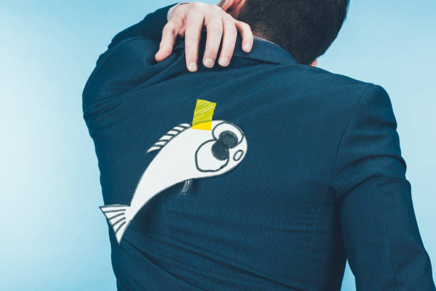 back view of businessman in suit with paper made fish on back, april fools day concept - april fools stock photos and pictures