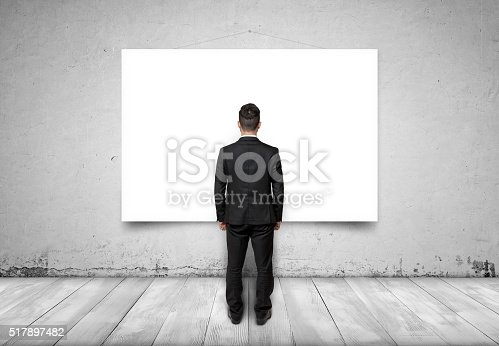 istock Back view of businessman looking at white empty canvas on 517897482