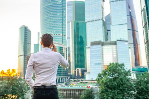 Rückblick auf Geschäftsmann, der auf Kopierplatz schaut, während er gegen Glas-Wolkenkratzer steht – Foto