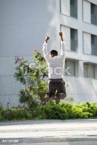 istock Back View of Businessman Raising Arms and Jumping 847161088