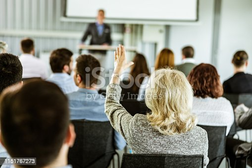 istock Back view of businesswoman asking a question on training class in a board room. 1151767273