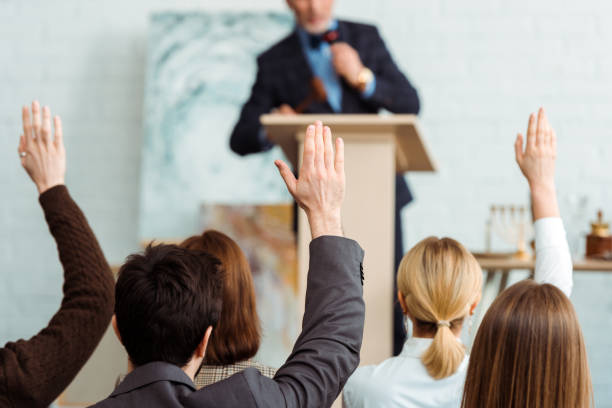 back view of buyers raising hands to auctioneer during auction back view of buyers raising hands to auctioneer during auction auction stock pictures, royalty-free photos & images