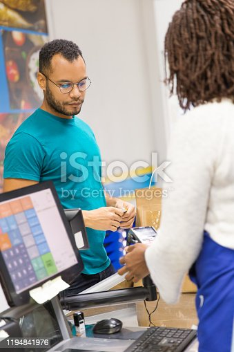 istock Back view of cashier using card reader at checkout 1194841976